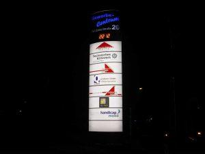 Pylon mit Firmenwerbung und digitaler Temperaturanzeige